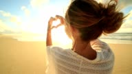 Young woman frames sunset on beach into heart shape video