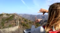 Young woman framing Great Wall of China with fingers video