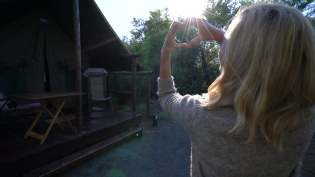 Young woman framing sunrise in heart shape video
