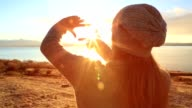 Young woman framing sunrise video
