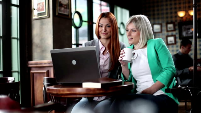 Young woman friends in cafe using laptop video