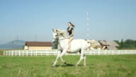 SLOW MOTION: Young woman galloping bareback with her beautiful white horse video
