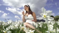 SLOW MOTION: Young woman gathering and smelling flowers video
