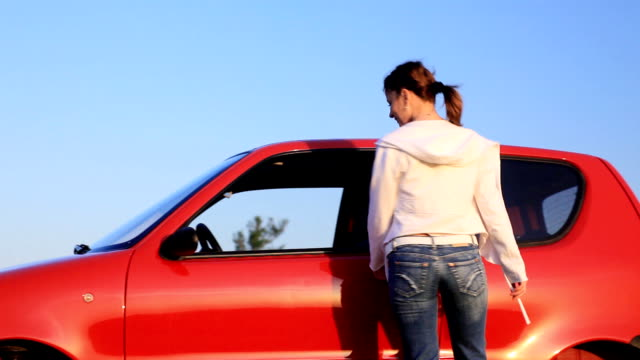 Young woman geting into the car  and driving. video