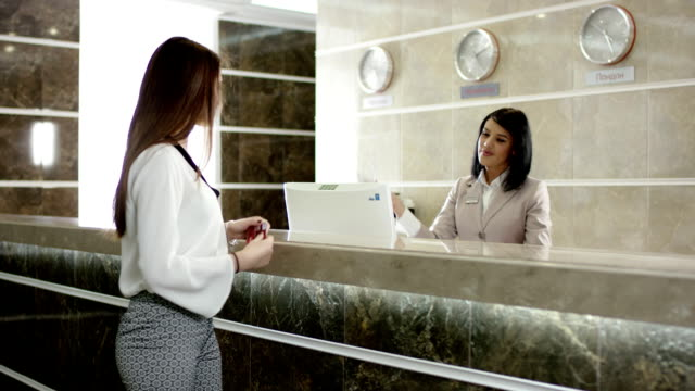 young woman gets a key in hotel for room video