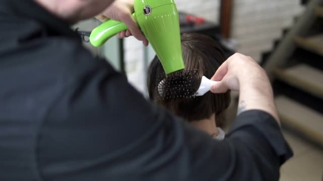 Young woman getting her hair dressed in hair salon. Hair stylist with a hairdryer. Hairdresser with hair dryer. Hairdresser at work. Beauty saloon. Shot in slowmotion video