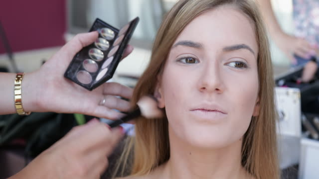 A young woman getting her makeup done video
