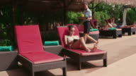 Young woman, girl relaxing in hotel swimming pool, holiday video