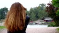 Young woman go in Helsinki park and talk on cellphone, slow motion video