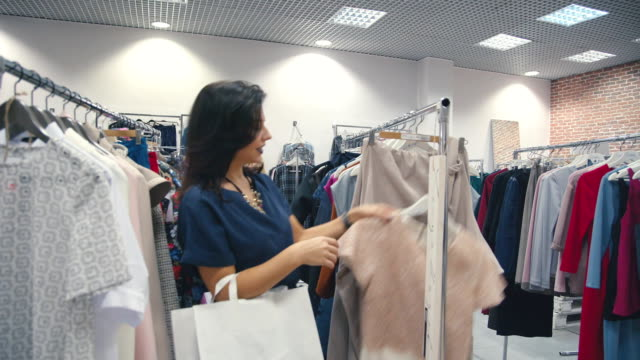 Young woman goes past the racks of clothes and find the nice dress video