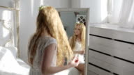 Young woman hair in front of the mirror video