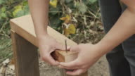 A young woman hammering nails into a frame in 4K. video