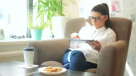 Young woman having a break and using a digital tablet. video