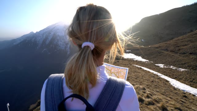 Young woman hiking in Switzerland looking at map video