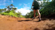 LOW ANGLE VIEW: Young woman hiking on dirt path through lush jungle forest video