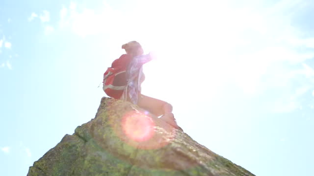 Young woman hiking on mountain peak-Success and freedom video
