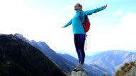 Young woman hiking reaches the mountain top, celebrates video