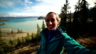 Young woman hiking reaches view point and takes selfie portrait video