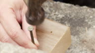 A young woman hits a nail into wood in slow motion. video