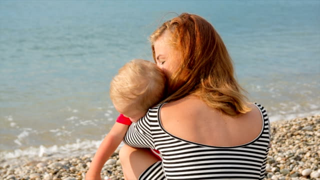 Young woman holding a child on the sea background video