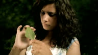 Young woman holding a leaf in nature and thinking video