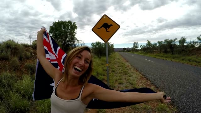 Young woman holding Australian flag in air near Kangaroo sign video