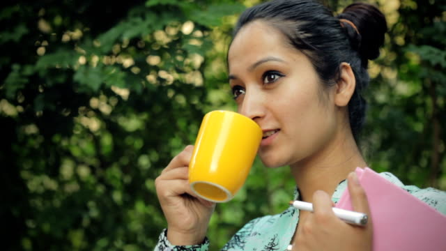 Young woman holding book, enjoying coffee in fresh air. video