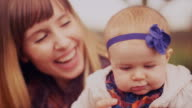 A young woman holding her baby daughter outdoors on a fall day and smiling video