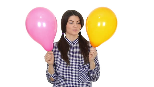Young woman holding two colorful balloons. video