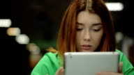 A young woman holds a finger on the touch screen tablet PC, stares at the screen and looks up video