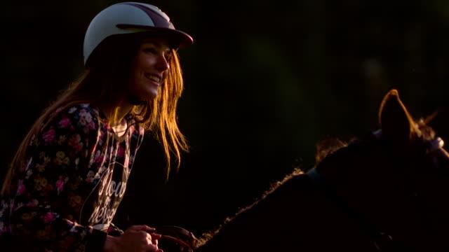 Young woman horseback riding at sunset video
