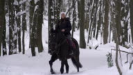 Young woman horseback riding through forest video