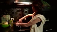 Young woman housewife stirring a meal in a cooking pot on the hot plate in the kitchen video