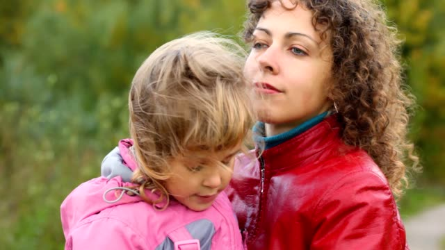 Young woman hugs little daughter in the wind outdoors video