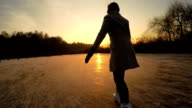 CLOSE UP: Young woman iceskating fast on big frozen pond in local park at sunset video