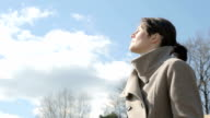 young woman in a coat standing outside and enjoying nature video