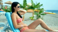 A young woman in a swimsuit relaxing on a deckchair on the beach. video