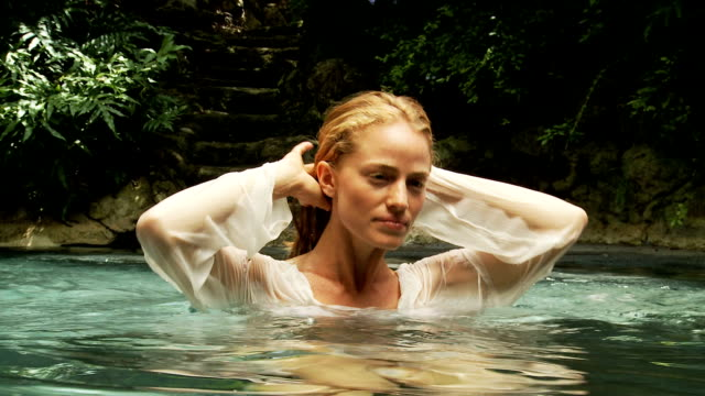 Young woman in a tropical pool video