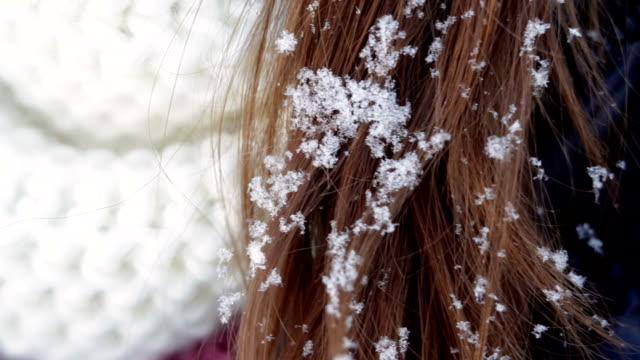 young woman in a white hat and a scarf and snow on her hair video