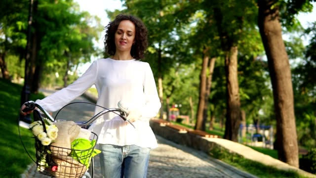 Young woman in a white t-shirt and blue jeans walking holding her city bicycle's handlebar with flowers in its basket in the city early in the morning. Slowmotion shot video