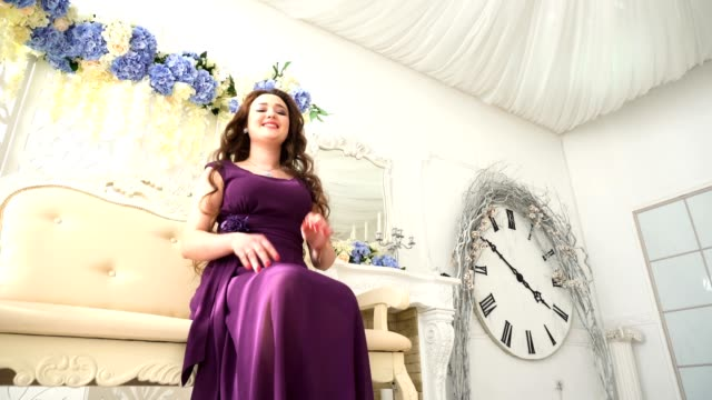 Young woman in an evening dress purple sitting on couch in luxury Interior video