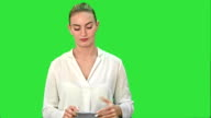 Young woman in anger rips a sheet of paper, throw it at the camera on a Green Screen, Chroma Key video