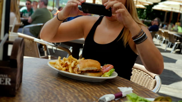 Young Woman in Baseball Hat Photos Her Meal at Outdoor Restaurant video
