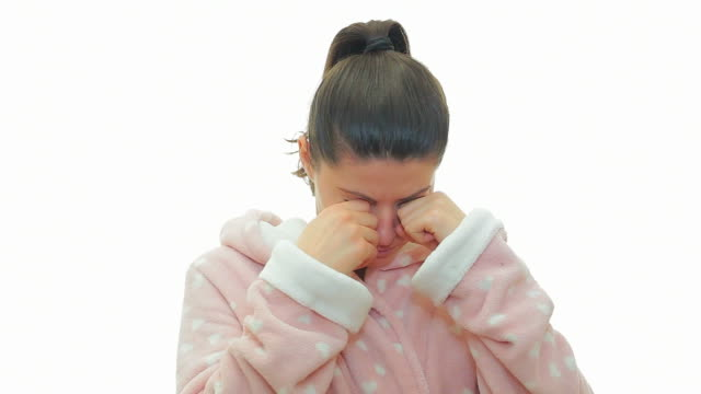 Young woman in bathrobe yawning on white background. video