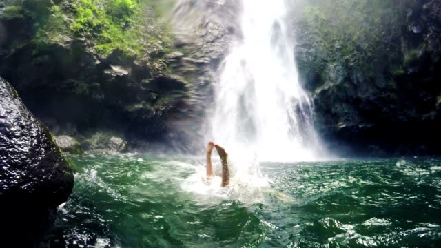 Young Woman In Bikini Dives into Big Powerful Waterfall Pond (Slow Motion) video