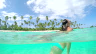 4K SLOW MOTION HALF UNDERWATER CLOSE UP: Young woman in bikini diving under the sea and swimming up to the surface on summer holidays on fantastic tropical island with exotic white sand beaches video
