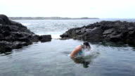 SLOW MOTION: Young woman in bikini splashing water with hair playfully video