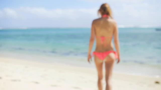 Young woman in bikini walking on a sandy beach video