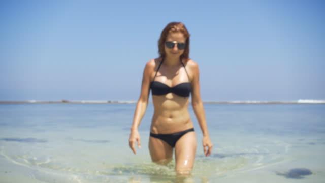 Young woman in bikini walking out of the ocean video