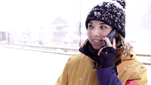 Young woman in bright winter clothes talks on the phone outside while it is snowing heavily video